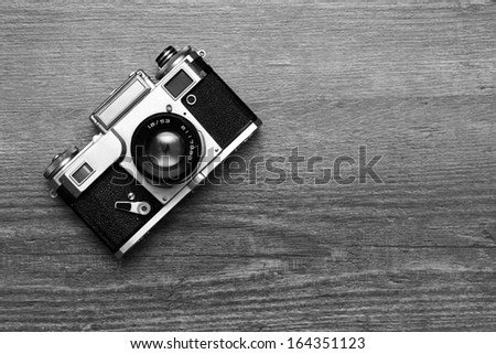 Vintage photo camera on a wooden background, black and white - stock photo