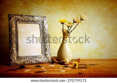 Vintage photo frame and flowers on wooden table over grunge background, Still life style  - stock photo