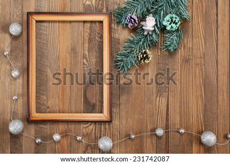 Vintage photo frame on wooden background with fir tree branch and christmas decorations - stock photo