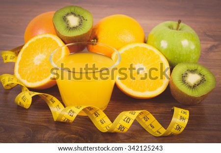 Vintage photo, Fresh ripe fruits, glass of juice and tape measure on wooden surface plank, grapefruit orange kiwi apple, healthy lifestyles nutrition and strengthening immunity - stock photo