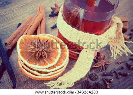 Vintage photo, Glass of mulled wine wrapped scarf with fresh fragrant spices, cinnamon vanilla anise cloves dried orange, drink on winter evening - stock photo