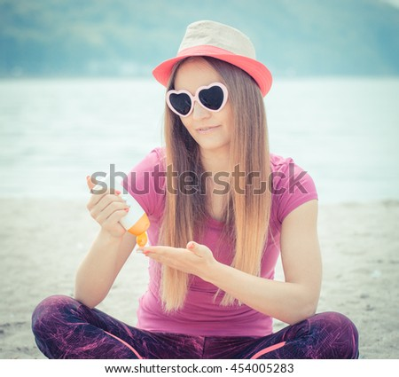 Vintage photo, Happy girl wearing straw hat and sunglasses in shape of heart on seaside and using sun lotion, sun protection on beach - stock photo