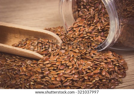 Vintage photo, Heap of brown linseed, flax seeds spilling out of glass jar on wooden background, concept for healthy nutrition - stock photo