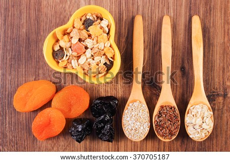 Vintage photo, Linseed, rye flakes and oat bran on spoon, dried fruits and muesli, concept of healthy nutrition and increase metabolism, ingredients with dietary fiber - stock photo