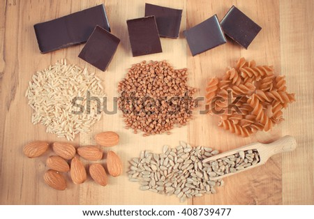 Vintage photo, natural ingredients and products containing magnesium and dietary fiber, healthy food and nutrition, wholemeal pasta, buckwheat, brown rice, sunflower, almonds, chocolate - stock photo