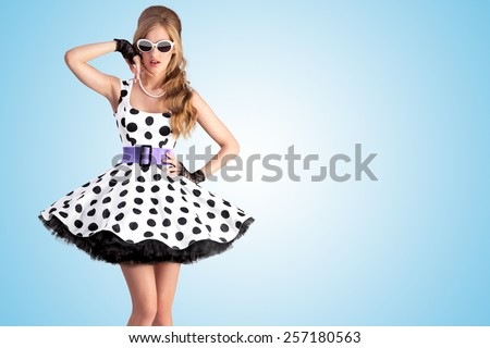 Vintage photo of a beautiful pin-up girl wearing a retro polka-dot dress and sunglasses, posing on blue background. - stock photo