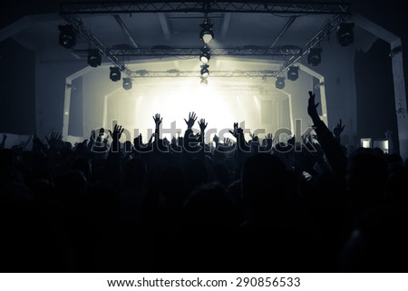 Vintage photo of a raised hands silhouettes at the rock concert, clubbing or celebrating New Year's eve. Active night life concept, higher ISO image, selective focus. No recognizable people. - stock photo