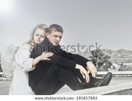 Vintage photo of angel woman embraces upset unfortunate man - stock photo