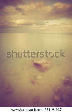 Vintage photo of beautiful long exposure landscape of rocky sea shore. Tranquil scene of Baltic sea near Gdynia in Poland.  - stock photo