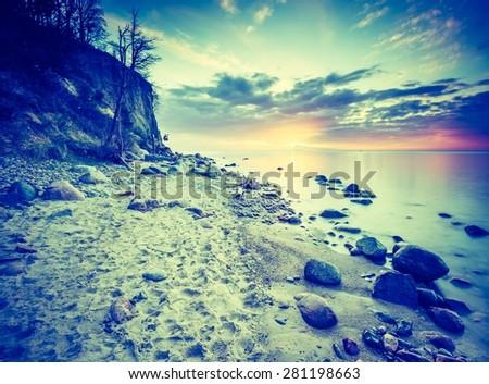 Vintage photo of beautiful rocky sea shore at sunrise or sunset. Long exposure landscape. Baltic sea near Gdynia in Poland. - stock photo