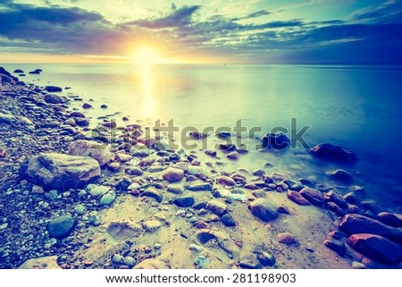 Vintage photo of beautiful rocky sea shore at sunrise or sunset. Long exposure landscape. Baltic sea near Gdynia in Poland. - stock photo