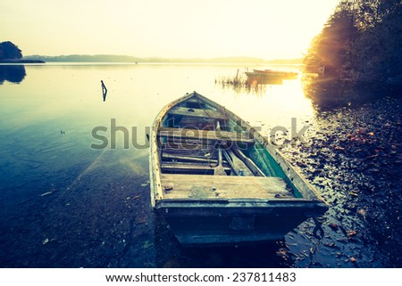 vintage photo of boat on lake at sunset - stock photo