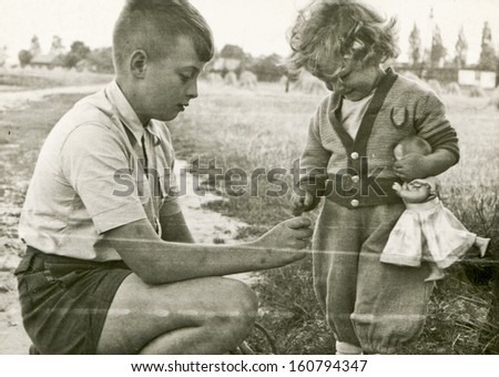 Vintage photo of brother and little sister with doll - fifties - stock photo