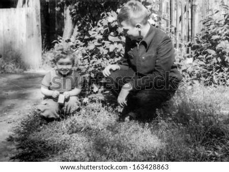 Vintage photo of brother playing outdoor with little sister, fifties - stock photo