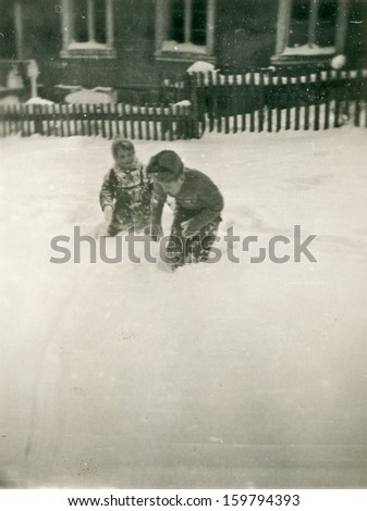 Vintage photo of brothers playing in snow, fifties - stock photo