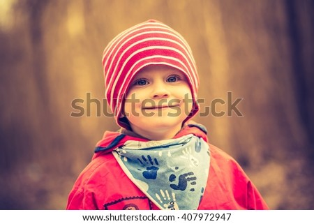 Vintage photo of caucasian boy playing outdoor. Portrait of happy boy playing in springtime landscape. - stock photo