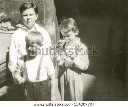 Vintage photo of children eating ice cream (early eighties) - stock photo