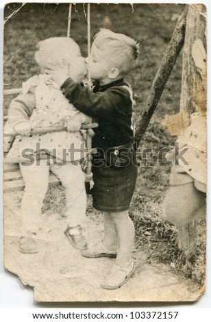 Vintage photo of children kissing (fifties) - stock photo