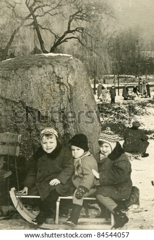 Vintage photo of children on sled (fifties) - stock photo