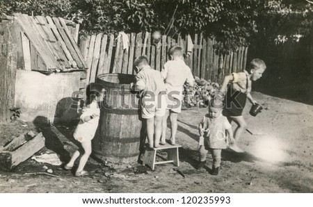 Vintage photo of children playing with big barrel (fifties) - stock photo