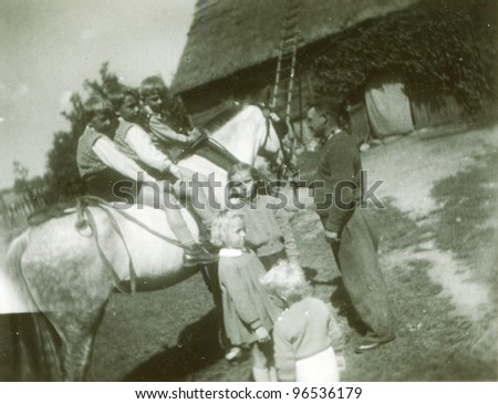 Vintage photo of children riding a horse in farm (fifties) - stock photo