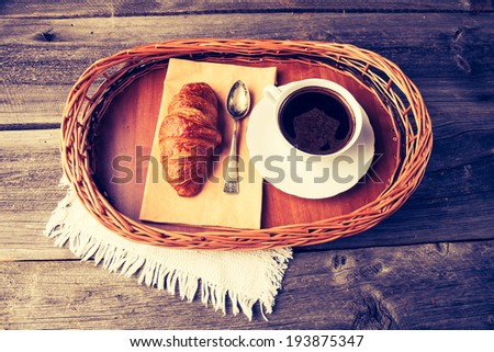 vintage photo of coffee and croissant. breakfast table - stock photo