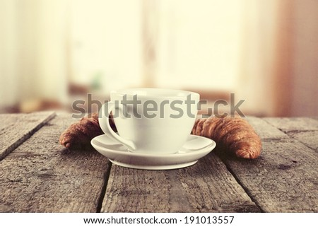 vintage photo of coffee and croissants with sun in window  - stock photo