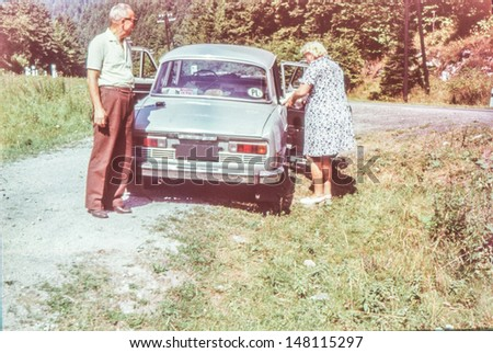 Vintage photo of couple with a car, sixties - stock photo
