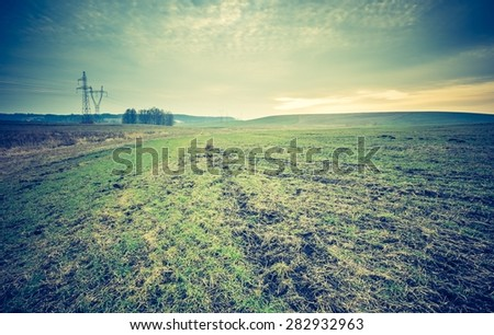 Vintage photo of dry grass field. Photo with old colors mood.Cultivated land in early spring  - stock photo