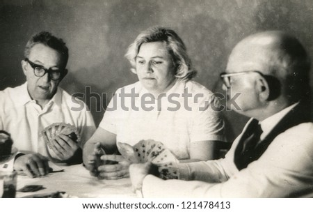 Vintage photo of elderly man playing cards with his daughter and son-in-law (sixties) - stock photo