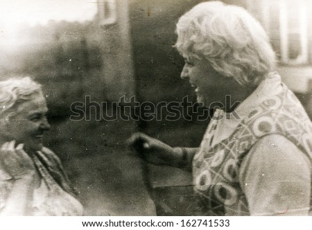 Vintage photo of elderly mother and adult daughter laughing , sixties - stock photo