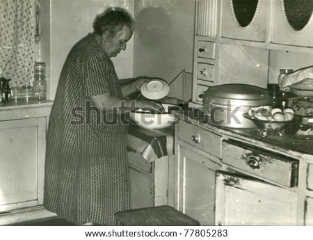 Vintage photo of elderly woman washing dishes in old-fashioned kitchen (fifties) - stock photo