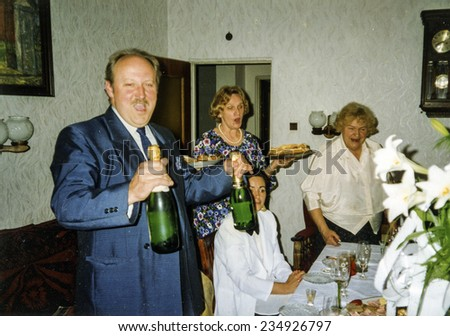 Vintage photo of family celebrating elderly couple's wedding anniversary, eighties - stock photo
