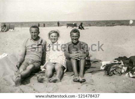 Vintage photo of family on beach (sixties) - stock photo