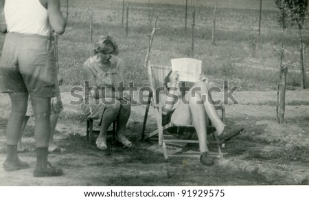 Vintage photo of family relaxing outdoor (fifties) - stock photo