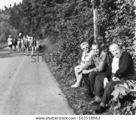 Vintage photo of family resting on bench (fifties) - stock photo
