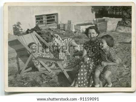 Vintage photo of family resting outdoor (fifties) - stock photo