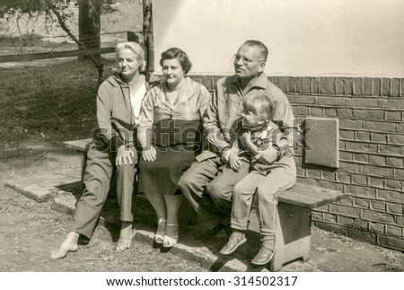 Vintage photo of family sitting on bench, 1950's - stock photo