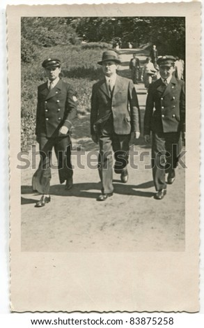Vintage photo of father and sons in school uniforms walking on the street (thirties) - stock photo