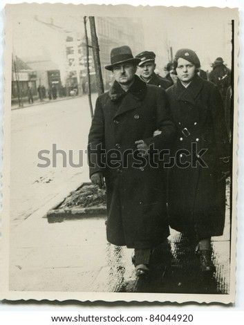 Vintage photo of  father, daughter and son walking on the street (thirties) - stock photo