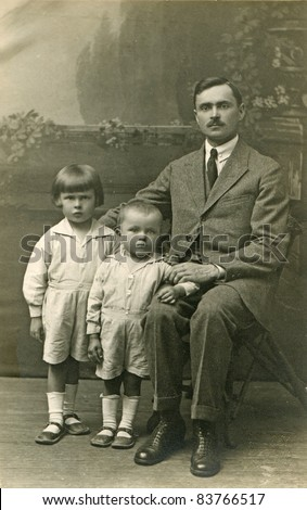 Vintage photo of father with sons (twenties) - stock photo