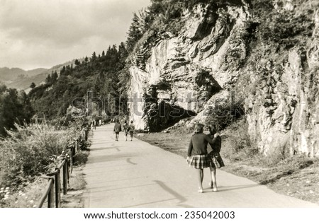 Vintage photo of girls walking in mountains, sixties - stock photo