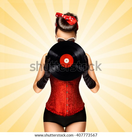 Vintage photo of glamorous pinup girl wearing long gloves and dressed in a red sexy corset, hiding behind LP vinyl record on colorful abstract cartoon style background. - stock photo