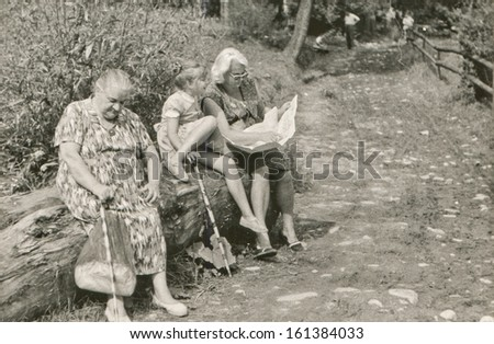 Vintage photo of grandmother, mother and daughter resting on tree trunk and reading - stock photo