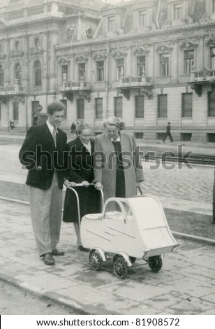 Vintage photo of happy couple with friend and baby in antique pram (fifties) - stock photo