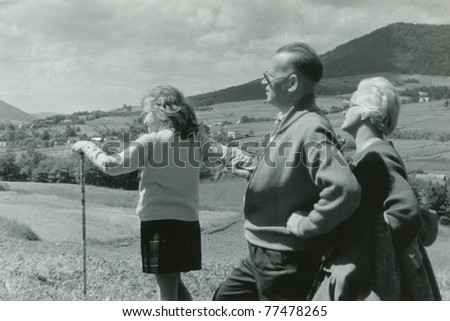 Vintage photo of happy family walking in mountains (early sixties) - stock photo