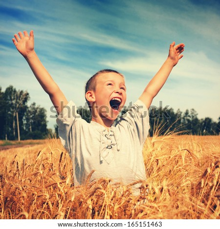 Vintage photo of Happy Kid in the Wheat Field - stock photo