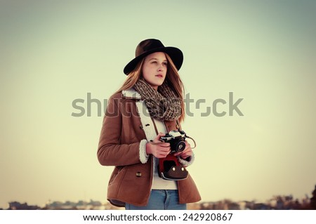 Vintage photo of hipster young girl photographer with old photo camera on a sunny winter day - stock photo