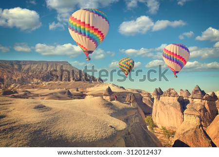 Vintage photo of hot air balloon flying over rock landscape at Cappadocia Turkey. - stock photo