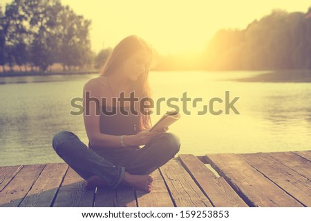 Vintage photo of learning young woman on wooden pier at the lake in sunset - stock photo
